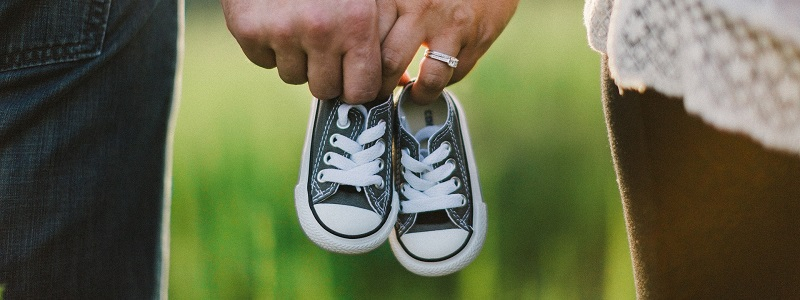a husband and wife holding baby shoes